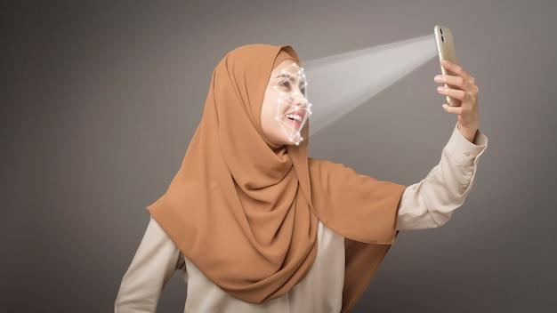 아름 다운 여자는 얼굴 인식 시스템 스마트 폰으로 그녀의 얼굴을 스캔