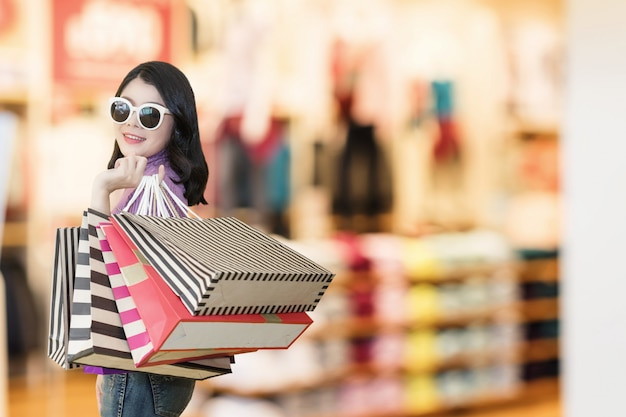 Beautiful woman is shopping in the mall using credit card.woman wearing glasses and holding shopping bag fashion