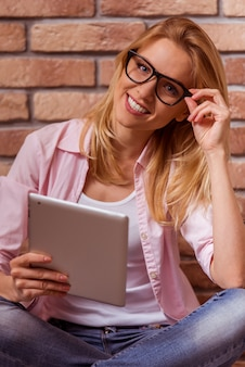 Beautiful woman is sitting cross-legged with tablet.