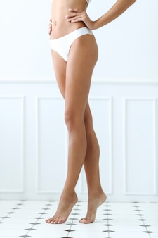 아름다운 여자가 욕실 타일에 맨발로 서있다