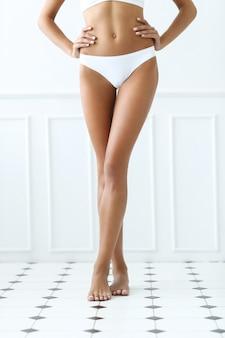 Bella donna è in piedi a piedi nudi su una piastrella in un bagno
