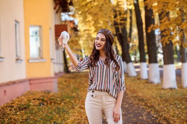 Красивая женщина принимает фотографии с помощью камеры instax. осеннее время