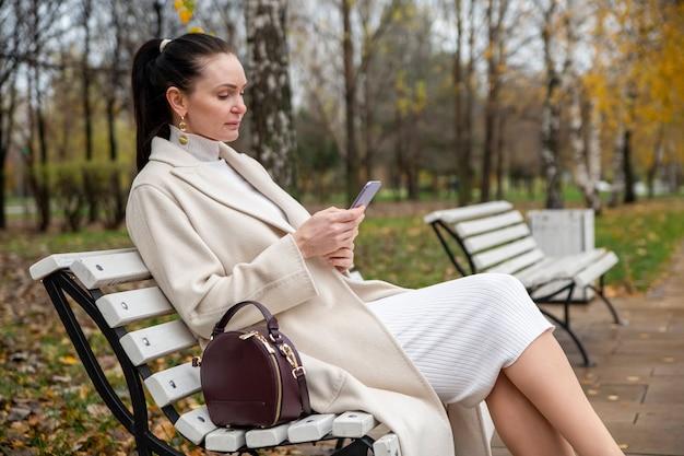 Красивая женщина печатает в смартфоне и сидит на скамейке в парке. блоггер создает контент. интернет серфинг. интернет-знакомства.