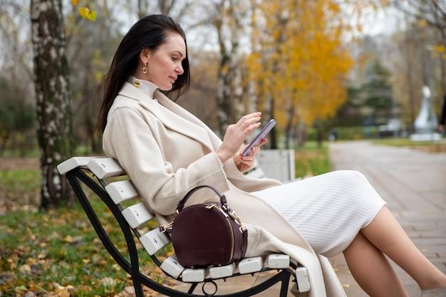 Красивая женщина печатает в смартфоне на скамейке в парке, блоггер создает контент для интернет-серфинга