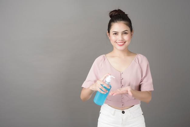 Красивая женщина использует спирт гель в студии