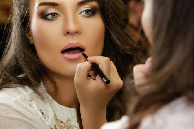 Beautiful woman is using pencil for lips