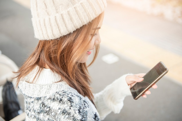 Beautiful woman is using smart phone on railway platform