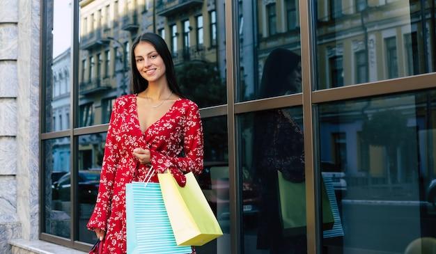 Красивая женщина идет по улице в красном цветочном платье, несет несколько сумок для покупок, улыбается и с нетерпением ждет