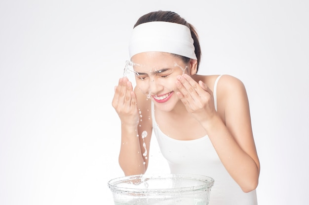 Beautiful woman is washing her face on white background