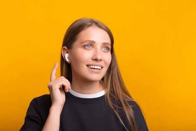 美しい女性は黄色の背景の上にいくつかのワイヤレスイヤーポッドを着ています。