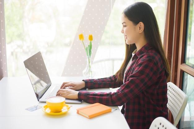 美しい女性はコーヒーショップでラップトップコンピューターで働いています。