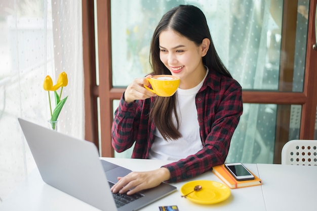 아름 다운 여자는 커피 숍에서 노트북 컴퓨터와 함께 작동