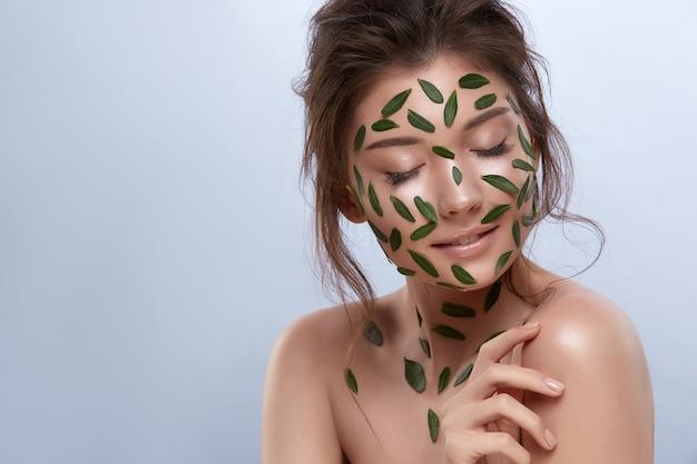 아래를 내려다 보면서 얼굴에 녹색 잎 회색에 고립 된 아름 다운 여자