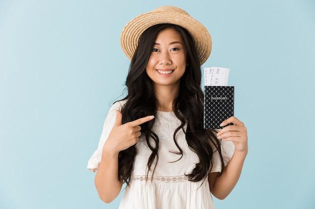Красивая женщина, изолированные на синей стене, держа паспорт с билетами, указывающими