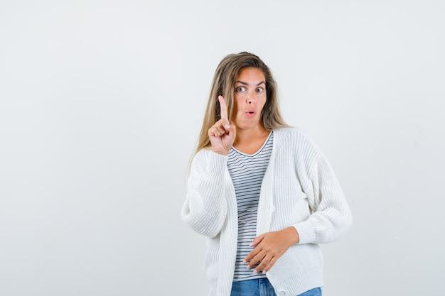 Bella donna in giacca puntare il dito verso l'alto e guardando sorpreso, vista frontale.