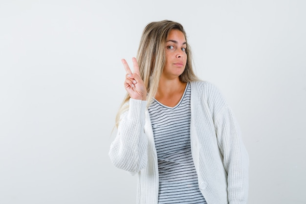 Beautiful woman in jacket showing v-sign gesture and looking cute , front view.
