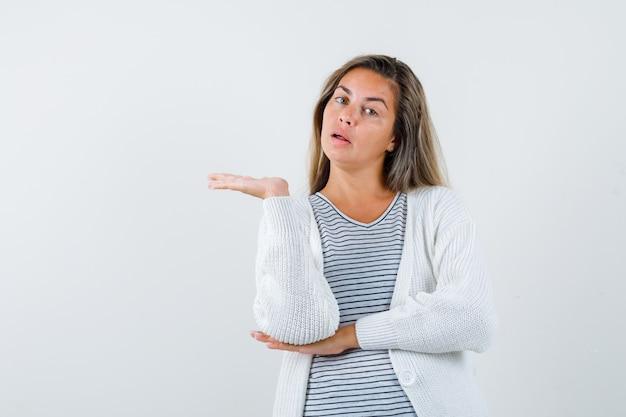 Bella donna in giacca che mostra gesto di benvenuto e che sembra sorpresa, vista frontale.