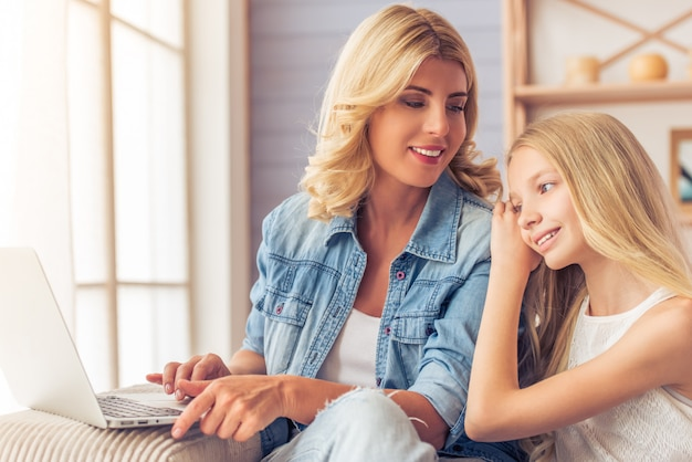Beautiful woman in jeans shirt and her daughter at home.