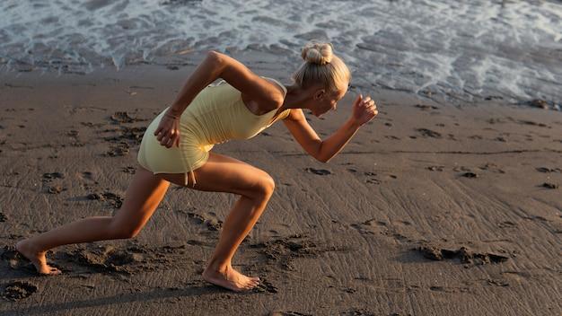 ビーチでジョギングする美しい女性。バリ