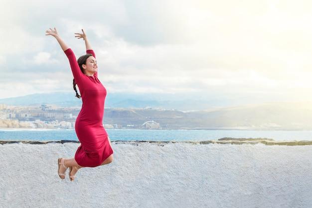 기쁨을 위해 점프하는 아름 다운 여자