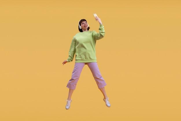 Beautiful woman jumping isolated on orange