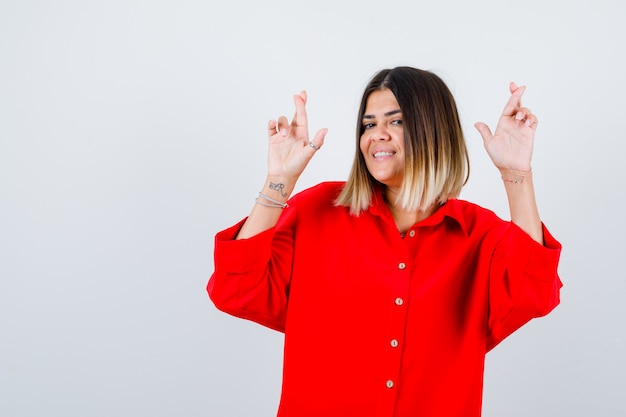 Beautiful woman keeping fingers crossed in red blouse and looking happy. front view.