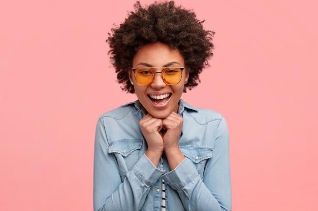 美しい女性は幸せから手をあごの下に保ち、前向きに笑い、パートナーからの良い提案を喜ぶ