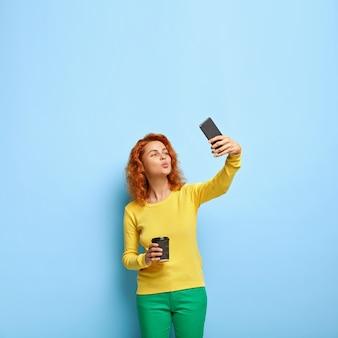 Красивая женщина держит губы сложенными перед камерой, фотографирует на современный мобильный телефон