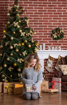 Beautiful woman in knitted dress sits on her lap and holds a new year's gift in her hands.