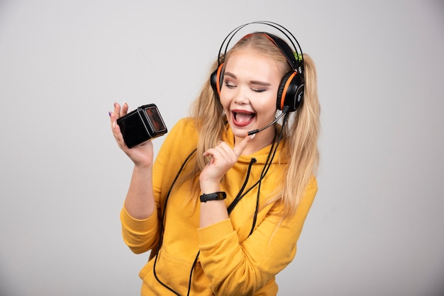 회색 배경에 헤드폰을 끼고 웃고 있는 아름다운 여자.