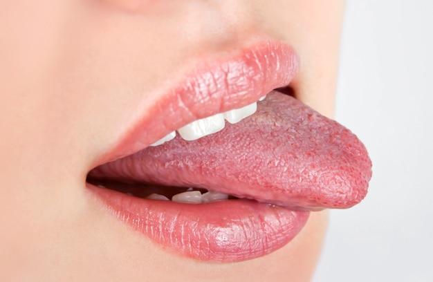 舌で歯を漏らしている美女がクローズアップ