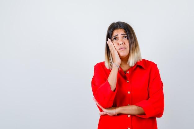 Bella donna appoggiata guancia sul palmo, alzando lo sguardo in camicetta rossa e guardando disperato, vista frontale.