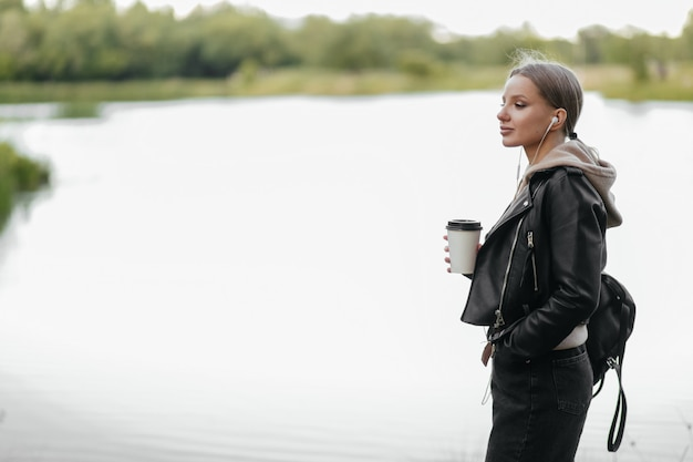 A beautiful woman in a leather jacket walks through the park with headphones and drinks coffee by the lake