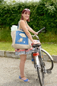 Beautiful woman leaving to the beach in bicycle