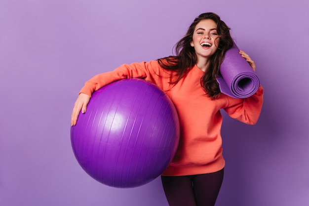 Beautiful woman in leggings and bright sweatshirt is smiling and posing with purple mat and fitball