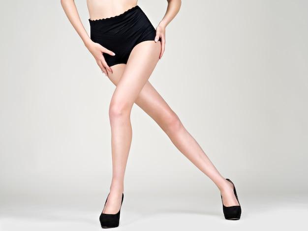 Belle gambe della donna in tacchi alti, mutandine nere - studio