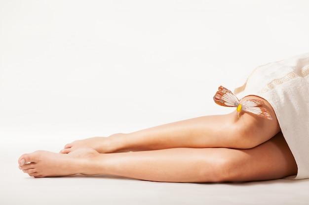 Красивая женщина ноги с бабочкой.