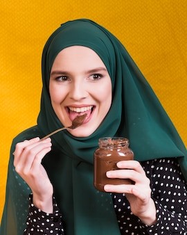Beautiful woman licking chocolate holding jar and spoon