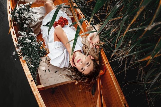 自然と引退する湖に浮かぶ木製のボートに一人で横たわる美しい女性