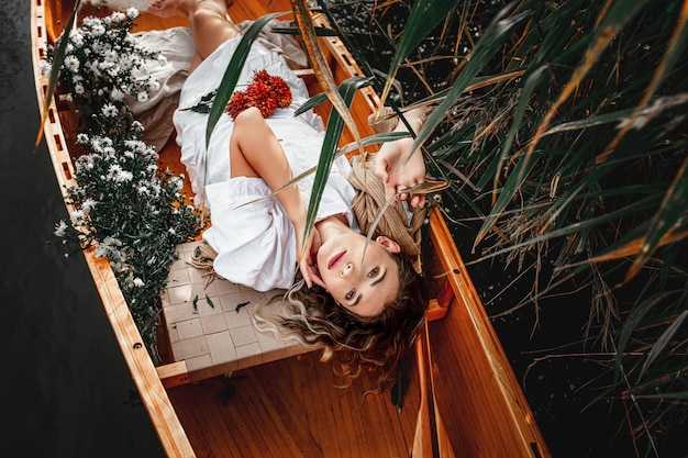 Beautiful woman lies alone in a wooden boat floating on the lake retiring with nature