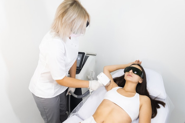 Beautiful woman lies in the couch of the laser epilation salon