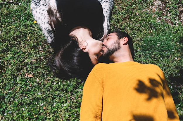 A beautiful woman lies and kisses a man on the ground
