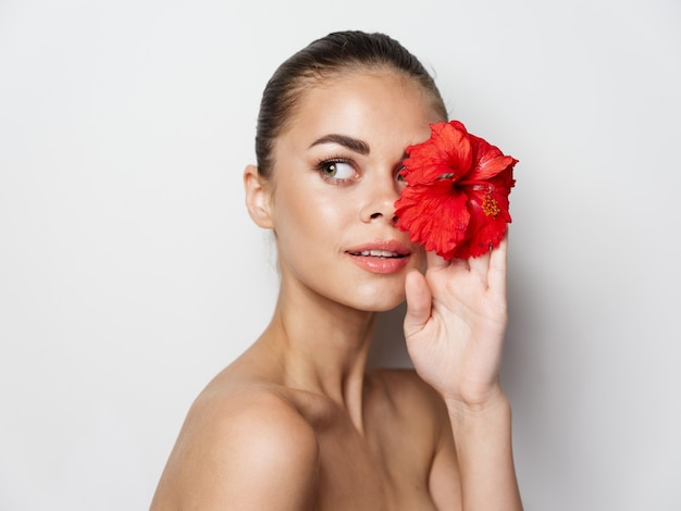 Beautiful woman on a light background with a flower in her hand cropped view