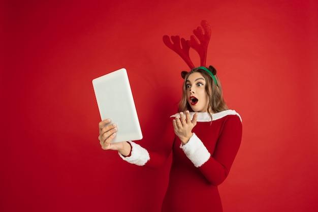 Красивая женщина, как рождественский олень, изолированные на красной поверхности концепция новогодних праздников зимнего настроения
