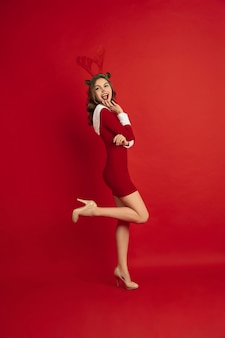 クリスマスの鹿のような美しい女性は、新年の冬の気分の休日の赤い表面の概念に分離されました