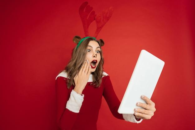 Красивая женщина, как рождественский олень, изолированные на красной стене концепции