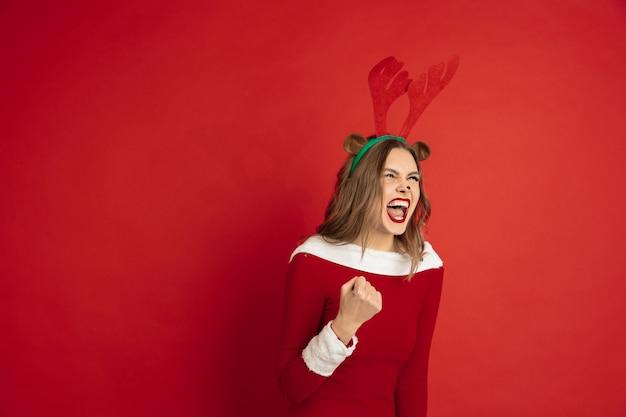 赤い壁の概念で隔離のクリスマス鹿のような美しい女性