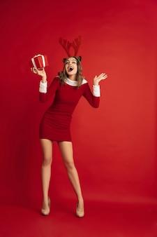 빨간 벽 개념에 고립 된 크리스마스 사슴 같은 아름 다운 여자