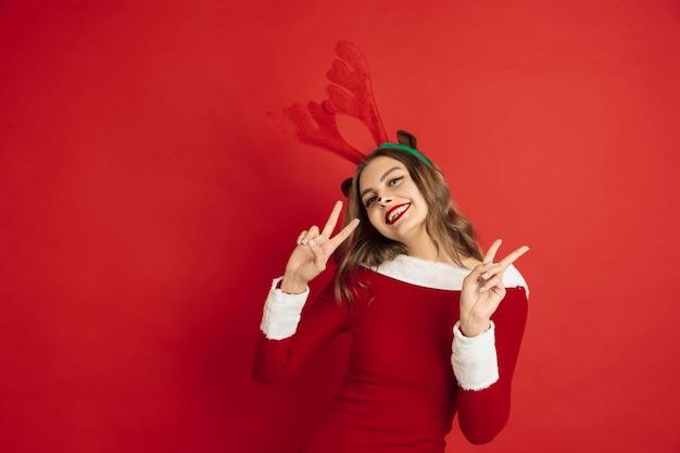 赤い壁に分離されたクリスマス鹿のような美しい女性