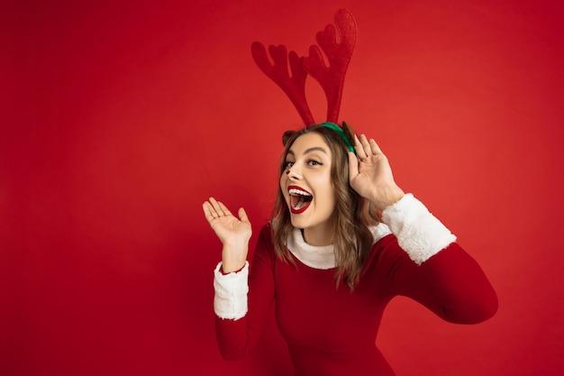 Красивая женщина, как рождественский олень, изолированные на красной стене